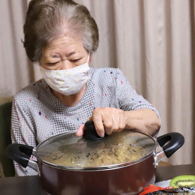 大きな鍋のフタをつかんで開けようとしている祖母・おばあ