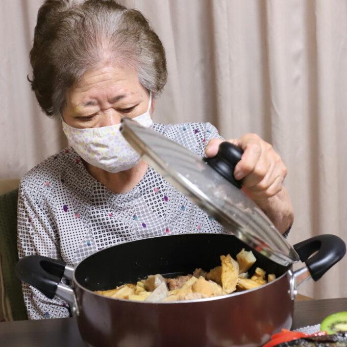 食卓で鍋のフタを開けている祖母・おばあ