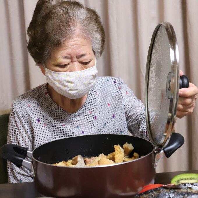 鍋のフタを開けている祖母