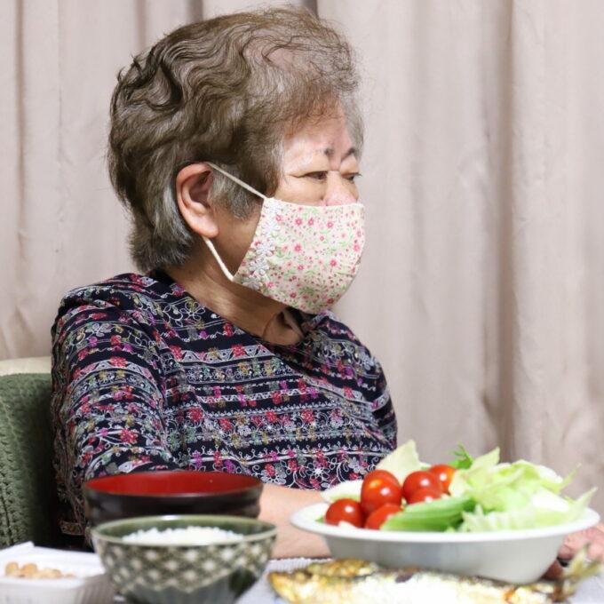 晩ごはんの食卓で、マスクを着けてテレビを見ている祖母