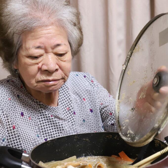 食卓に着いて鍋の蓋を開ける祖母・おばあ