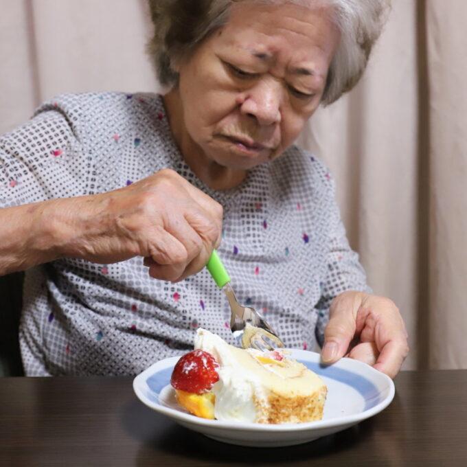 皿に切り分けたロールケーキを食べる祖母