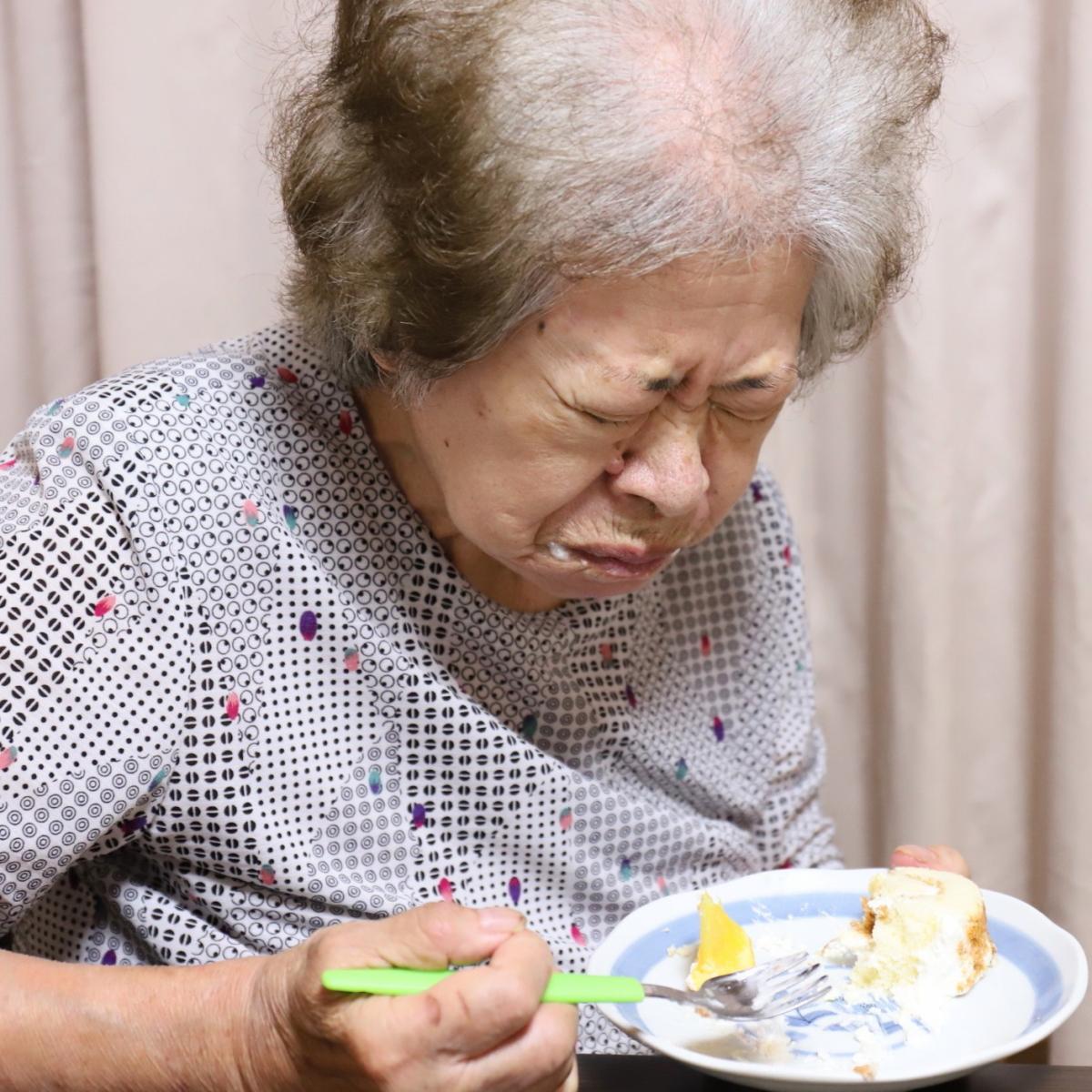ケーキのトッピングのオレンジを食べて顔をしかめる祖母