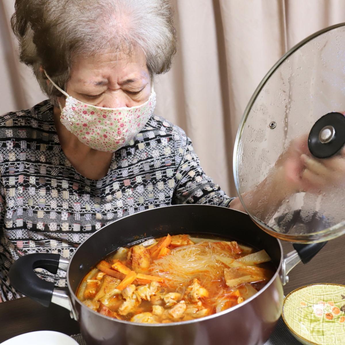 鍋の蓋を開ける祖母とキムチ鍋