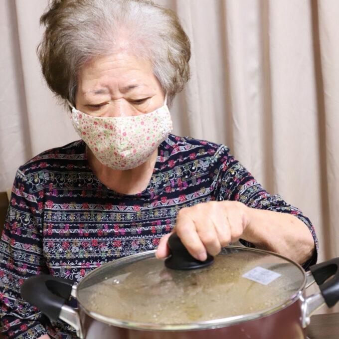 食卓で鍋のフタを開けようとしている祖母・おばあ