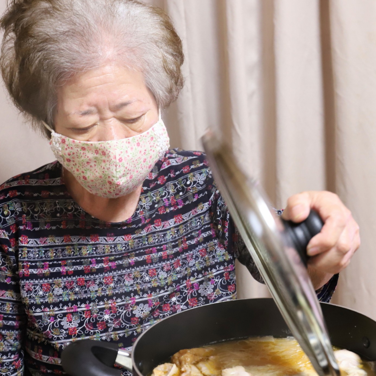 鍋のフタを片手で持って開けている祖母
