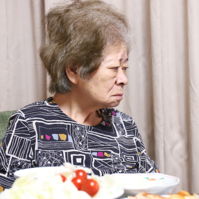 晩ごはんの食卓についている祖母・おばあの横顔