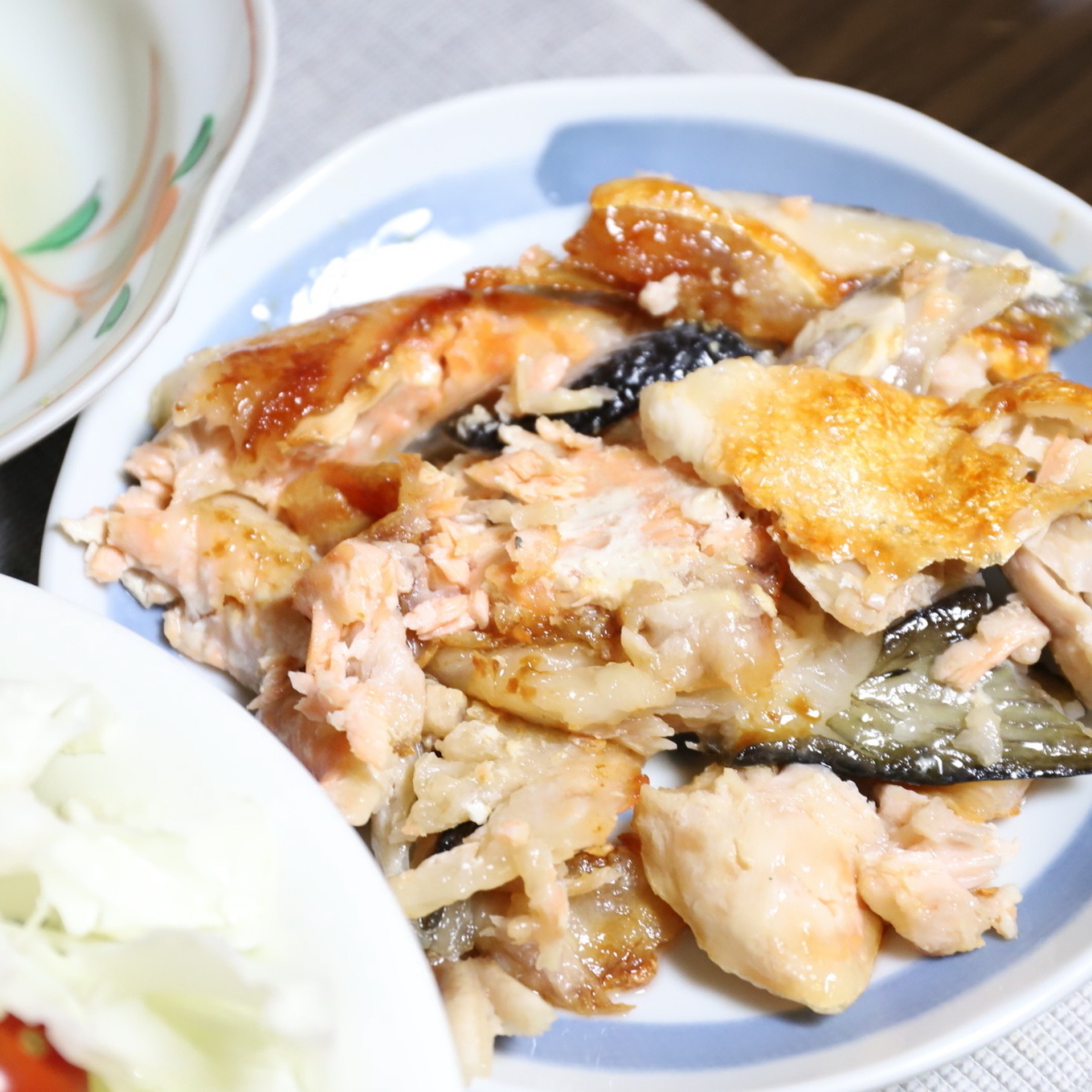 皿に乗っている鮭のアラを焼いたもの