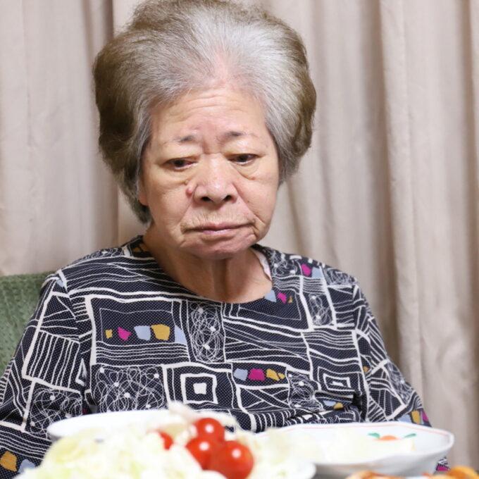 晩ごはんの食卓に着いてこちらを見ている祖母・おばあ