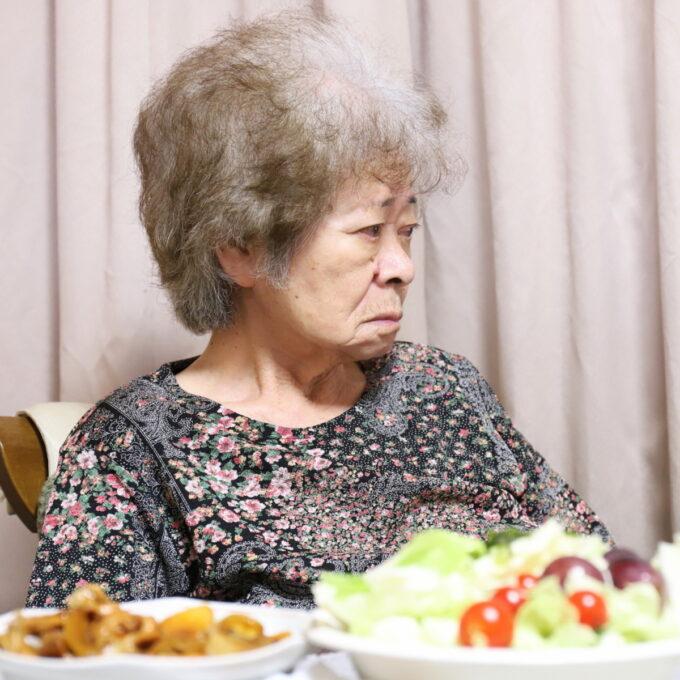 食卓に着いてテレビを見ている祖母・おばあ