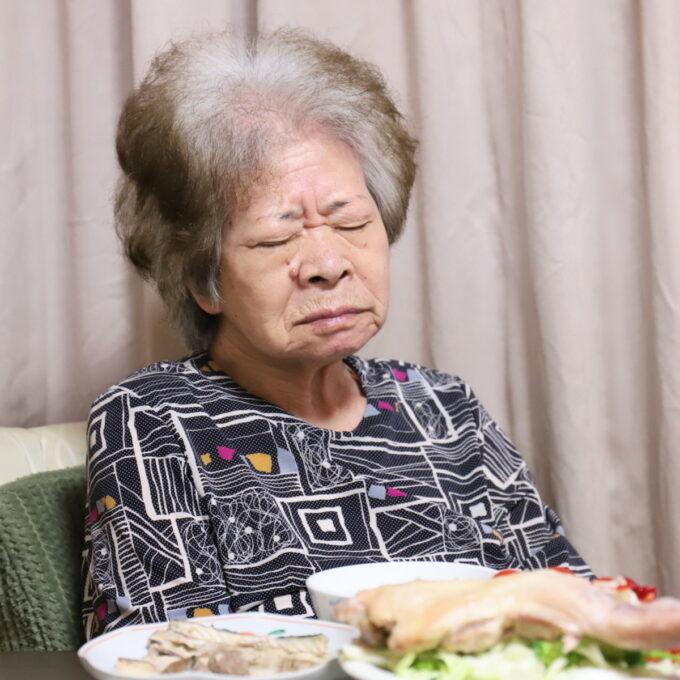 食卓に着いて目をつむって居眠りしている祖母・おばあ