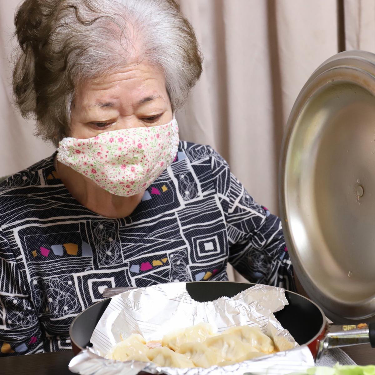 餃子を焼いたフライパンのフタを持ち上げる祖母・おばあ